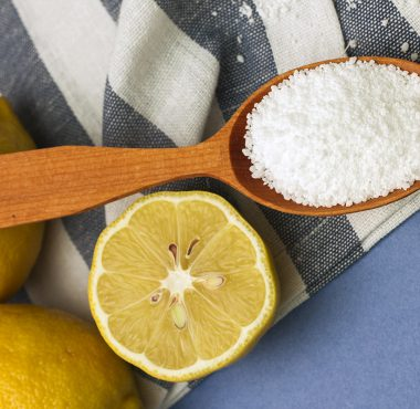 Citric acid in a spoon next to a lemon