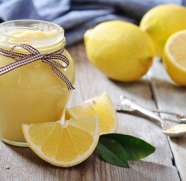Lemon curd in a jar with fresh lemons beside it