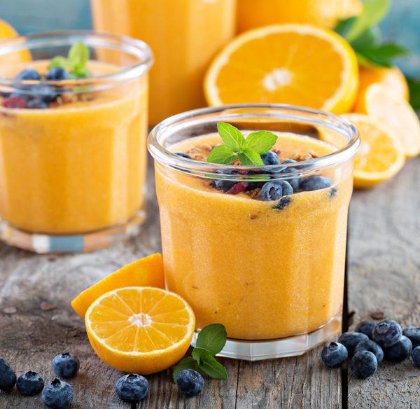 Orange sorbet in a jar with berries on top.