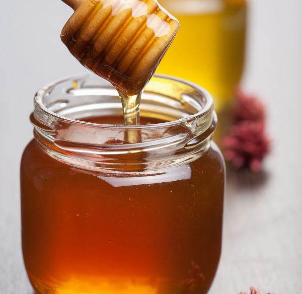 Raw Honey driping into a jar from a honey spoon.